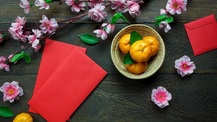 Top view accessories Chinese new year festival decorations.orange,leaf,wood basket,red packet,plum blossom on table wooden background with copy space.