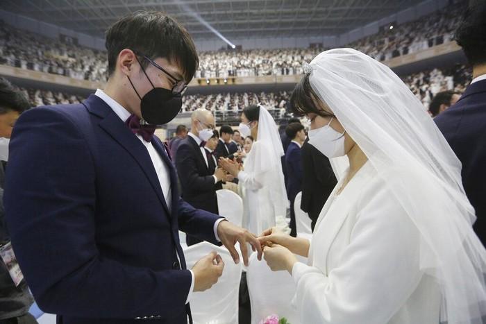 Sejumlah warga Korea Selatan ikuti kegiatan nikah massal. Meski kenakan masker untuk cegah virus corona, para pasangan pengantin tampak bahagia di acara itu.