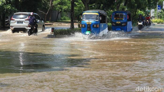 Pengendara melintasi banjir yang menggenangi Jalan Sunter Permai Raya atau di depan proyek pembangunan Stadion BMW, Jakarta Utara, Sabtu (8/2/2020).