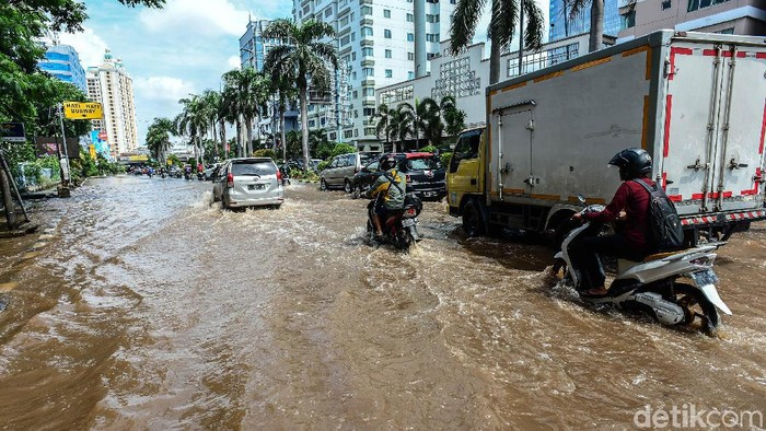 Pengendara melintasi banjir yang menggenangi Jalan Mitra Sunter Boulevard, Jakarta Utara, Sabtu (8/2/2020).   Air surut terpantau sekitar pukul 15.00 WIB.