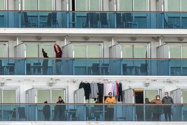 YOKOHAMA, JAPAN - FEBRUARY 07: A passenger jogs on the spot as another stretches as they wait on the balconies of their cabins on the Diamond Princess cruise ship as it sits docked at Daikoku Pier where it is being resupplied and newly diagnosed coronavirus cases taken for treatment as it remains in quarantine after a number of the 3,700 people on board were confirmed to have coronavirus, on February 7, 2020 in Yokohama, Japan. 61 passengers are confirmed to be infected with coronavirus as Japanese authorities continue screening people on board. The new cases bring the total number of confirmed infections to 86 in Japan, the largest number outside of China. (Photo by Carl Court/Getty Images)