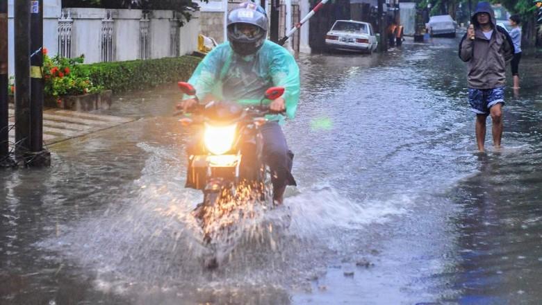 Pengendara sepeda motor melintas di jalan perumahan Komplek Ikip yang tergenang air di Duren Sawit, Jakarta Timur, Sabtu (8/2/2020). Genangan air setinggi 10-30 cm tersebut muncul akibat curah hujan yang tinggi dan saluran drainase menuju Kanal Banjir Timur yang buruk. ANTARA FOTO/ Fakhri Hermansyah