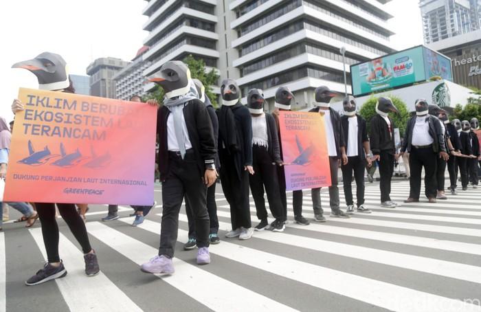 Aktivis Greenpeace Indonesia gelar aksi menggunakan kostum penguin di CFD Jakarta. Aksi itu digelar guna mendukung perjanjian laut internasional.