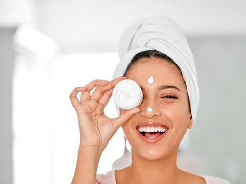 Shot of an attractive young woman covering her eye with a beauty product in her bathroom at home