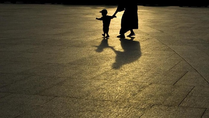 A young child and an adult walking across pavement at night while holding hands.  The silhouette and shadow of the two in the dark can be seen.