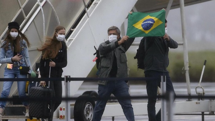 Brazilians hold a Brazilian flag after arriving from Wuhan, China, the epicenter of the coronavirus at the Annapolis Air Force Base, in Anapolis city, Goias state, Brazil, Sunday, Feb. 9, 2020. Dozens of Brazilians landed early Sunday morning at the airbase in the Brazilian state of Goias, where they will spend the next 18 days in quarantine. (AP Photo/Beto Barata)