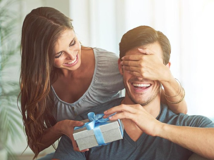 A young woman covering her husbands eyes for a surprise gift