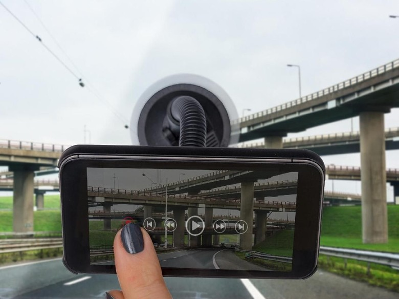Personal perspective mature womans hand rewinding a dashboard camera app with flyover on display  Photo on display and ui by contributor