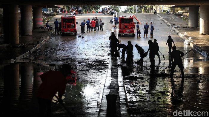 Sejumlah petugas membersihkan sisa lumpur dan air yang masih berada di underpass Kemayoran, Jakarta  Senin (10/2). Menurut keterangan petugas saat ini underpass Kemayoran belum bisa dilalui kendaraan karena masih dalam tahap pengeringan.