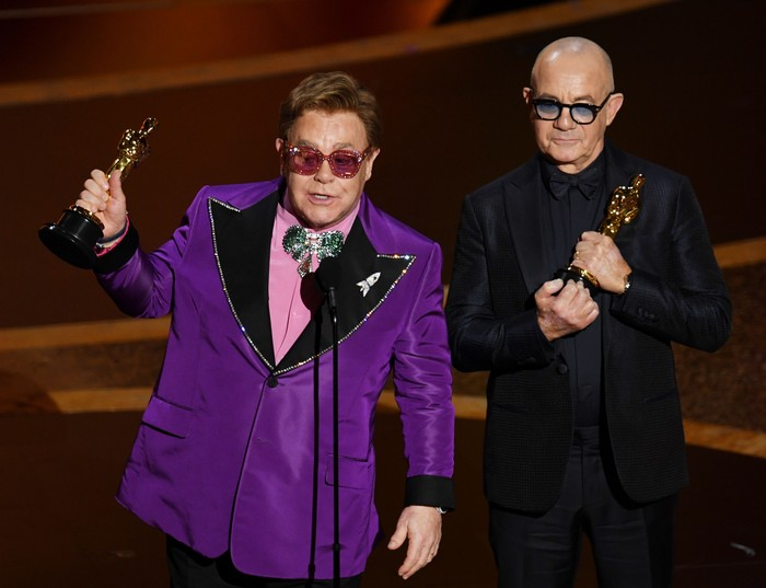 HOLLYWOOD, CALIFORNIA - FEBRUARY 09: (L-R) Elton John and Bernie Taupin accept the Music - Original Song - award for Im Gonna Love Me Again from Rocketman onstage during the 92nd Annual Academy Awards at Dolby Theatre on February 09, 2020 in Hollywood, California. (Photo by Kevin Winter/Getty Images)
