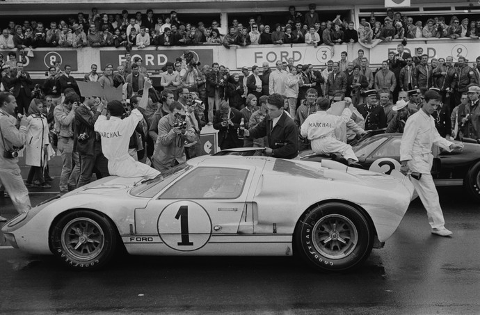 The crowd celebrating New Zealand racing drivers Bruce McLaren (1937 - 1970, left) and Chris Amon (1943 - 2016, right) with Ford CEO Henry Ford II (1917 - 1987, centre) on the podium after winning the 24 Hours of Le Mans, the 34th Grand Prix of Endurance in Le Mans, France, 19th June 1966. (Photo by Reg Lancaster/Daily Express/Hulton Archive/Getty Images)