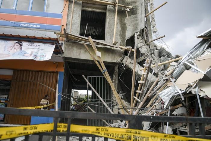 Warga melihat bangunan yang ambruk di Jalan Pisangan Baru, Matraman, Jakarta, Selasa (11/02/2020). Gedung berlantai tiga dalam proses pembangunan tersebut ambruk pada Selasa (11/2) pukul 11.00 WIB, sementara polisi masih menyelidiki penyebab kejadian. NTARA FOTO/Galih Pradipta/foc.