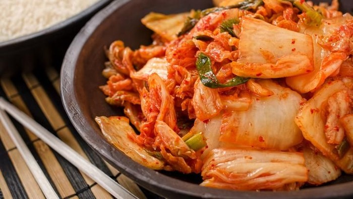 A bowl of traditional Korean napa kimchi with white rice.