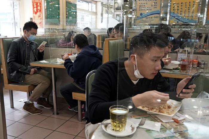 Demi mencegah penyebaran virus corona, beberapa restoran di Hong Kong memasang panel plastik transparan pada setiap meja.
