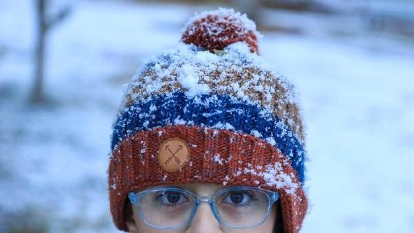 Potret seorang anak perempuan dengan topinya yang ditutupi salju. Menandakan betapa lebatnya salju yang turun saat itu (Mohammed Sawaf/AFP)