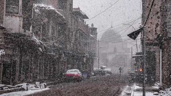 Suasana Jalan Sarjkhana di Kota Tua Mosul yang diselimuti hujan salju. Kota ini terletal di sisi Utara Irak (Zaid Al-Obeidi/AFP)
