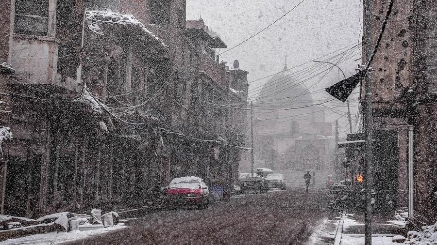 This picture taken on February 10, 2020 amidst a heavy snow storm shows a view along Sarjkhana street in the old town of Iraqs northern city Mosul with the background showing the dome of the Nuri mosque, which was heavily damaged by Islamic State (IS) group fighters in the 2017 battle for the city. (Photo by Zaid AL-OBEIDI / AFP)