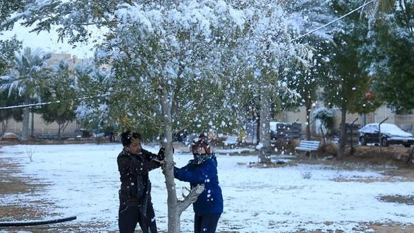 Seorang orang pria paruh baya yang tampak tengah bersenang-senang usai turun salju. Sementara teman lainnya sibuk mengabadikan momen tersebut (Mohammed Sawaf/AFP)