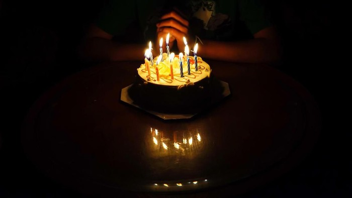 The boy is requesting blessings on his birthday by having a cake.