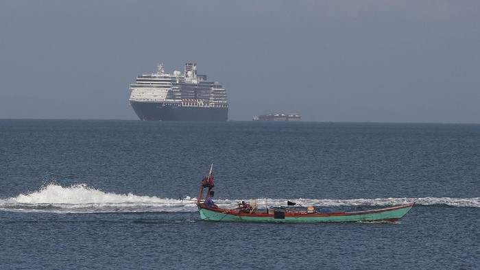 The MS Westerdam, owned by Holland America Line, sails off a port of Sihanoukville, Cambodia, Thursday, Feb. 13, 2020. Holland America Line said the ship has been turned away by the Philippines, Taiwan, Japan and Thailand, though its operator said no cases of the disease have been confirmed among the more than 2,200 passengers and crew. (AP Photo/Heng Sinith)