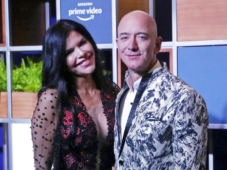FILE - In this Jan. 16, 2020, file photo, Amazon CEO Jeff Bezos, right and his girlfriend Lauren Sanchez poses for photographs during a blue carpet event organized by Amazon Prime Video in Mumbai, India. Michael Sanchez, the brother of Jeff Bezoss girlfriend, is suing the Amazon founder for defamation, alleging that Bezos and his team falsely told reporters that he provided nude photos of Bezos to the The National Enquirer.  (AP Photo/Rafiq Maqbool, File)
