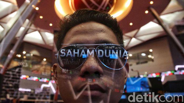 Pengunjung berada di sekitar layar pergerakan Indeks Harga Saham Gabungan (IHSG) di Bursa Efek Indonesia (BEI) Jakarta, Kamis (13/2). Indeks Harga Saham Gabungan (IHSG) di Bursa Efek Indonesia (BEI) hari ini pukul 12.00 menurun-0,67% ke posisi 5,873,30. Pergerakan IHSG ini masih dipengaruhi oleh sentimen atas ketakutan pasar akan penyebaran wabah virus corona.