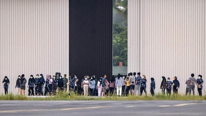 Sejumlah Warga Negara Indonesia (WNI) yang dievakuasi dari Wuhan, Hubei, China bersiap melakukan senam bersama prajurit TNI pada hari ketigabelas di Hanggar Pangkalan Udara TNI AU Raden Sadjad, Ranai, Natuna, Kepulauan Riau, Jumat (14/2/2020). Sekretaris Direktorat Jenderal Pencegahan dan Pengendalian Penyakit dr. Achmad Yurianto sudah diputuskan bahwa observasi WNI dari Wuhan yang saat ini tinggal di Natuna, berakhir pada tanggal 15 Februari 2020 pukul 12.00 WIB.  ANTARA FOTO/Muhammad Adimaja/foc.