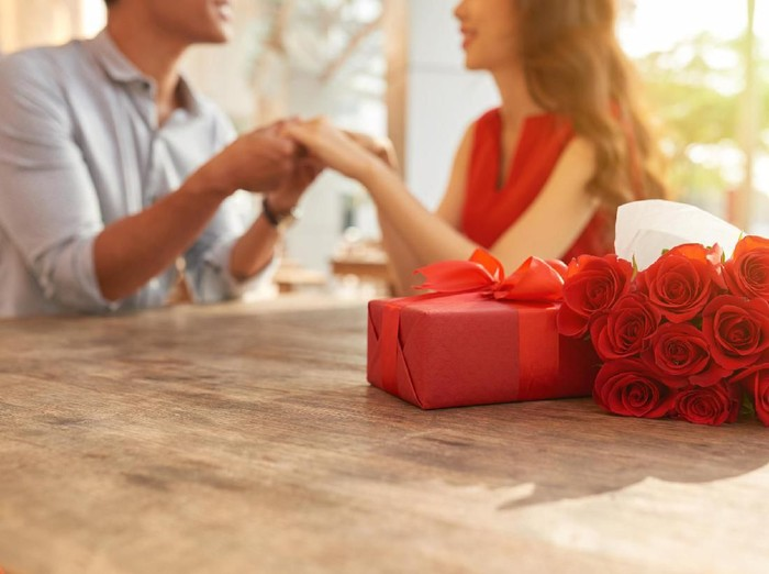 Cheerful young couple sitting at wooden table of outdoor cafe and holding hands while celebrating Valentines Day, gift box and bouquet of red roses on foreground