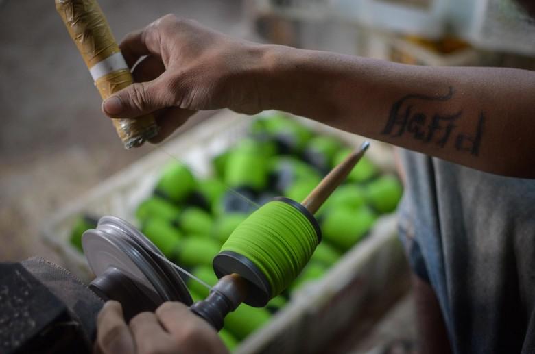 Perajin menggulung gelasan atau benang untuk layang-layang di Kampung Gelasan, Tanjungsari, Kabupaten Sumedang, Jawa Barat, Jumat (14/2/2020). Kampung Gelasan yang telah ada sejak 1990-an tersebut dapat memproduksi 500 lusin gelasan per hari yang dijual dari harga Rp3.000 hingga Rp20 ribu serta diminati oleh pehobi layang-layang adu di berbagai negara Asia Tenggara seperti Malaysia, Brunei Darussalam, dan Filipina. ANTARA FOTO/Raisan Al Farisi/foc.