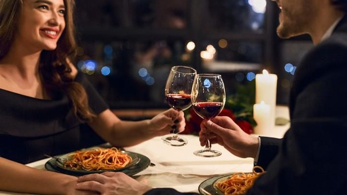 Young couple in a restaurant, drinking wine. Both about 25 years old, Caucasian.