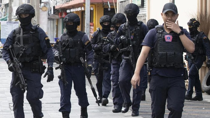 Police in tactical gear leave the site of a shooting in Bangkok, Thailand, Friday, Feb. 14, 2020. Multiple gunshots were fired in the air by a man in the middle of the capital Bangkok, police said Friday. The man suspected of firing some 20-40 shots was refusing to surrender more than six hours later. (AP Photo/Sakchai Lalit)
