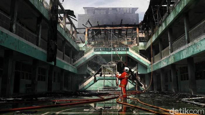 Petugas pemadam kebakaran berusaha memadamkan api di kawasan Sekolah Sentosa, Taman Sari, Mangga Besar, Jakarta, Sabtu (15/2). Kebakaran tersebut terjadi pada pukul 08.00 WIB. Penyebab kebakaran masih diselediki.