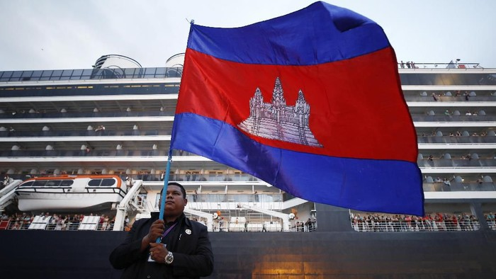 A Cambodian man holds his national flag in front of the MS Westerdam, owned by Holland America Line, dockked at the port of Sihanoukville, Cambodia, Friday, Feb. 14, 2020. Hundreds of cruise ship passengers long stranded at sea by virus fears cheered as they finally disembarked Friday and were welcomed to Cambodia. (AP Photo/Heng Sinith)