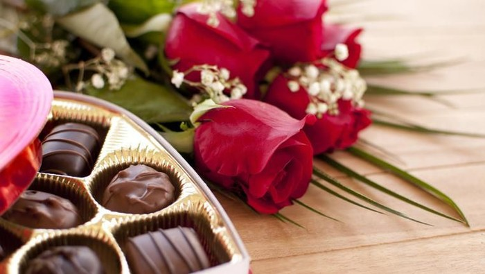 Red roses and chocolate candy on a wooden table