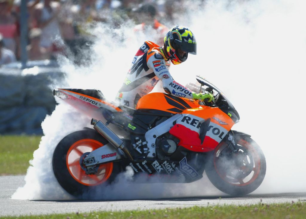 DONINGTON, ENGLAND - JULY 13:   Valentino Rossi of Italy and Repsol Honda celebrates winning the Cinzano British Moto GP on July 13, 2003 at Donington Park, England. (Photo by Clive Rose/Getty Images).