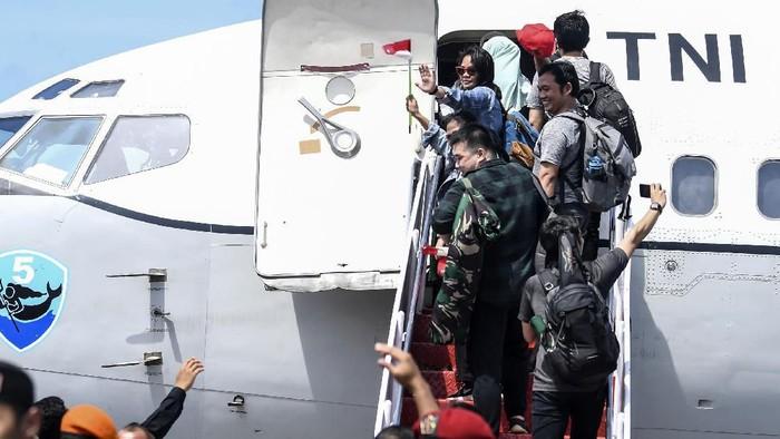 Sejumlah prajurit TNI bersama masyarakat mengibarkan bendera merah putih saat melepas Warga Negara Indonesia (WNI) yang telah selesai menjalani masa observasi usai dievakuasi dari Wuhan, Provinsi Hubei, China di Hanggar Pangkalan Udara TNI AU Raden Sadjad, Ranai, Natuna, Kepulauan Riau, Sabtu (15/2/2020). Pemerintah melalui Kementerian Kesehatan secara resmi telah memulangkan 238 WNI ke daerah masing-masing karena telah dinyatakan sehat. ANTARA FOTO/Muhammad Adimaja/wsj.