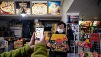 Turis datang tak cuma untuk makan, tapi sekaligus untuk foto di Sky Pizza yang digunakan syuting film Parasite. (ED JONES/AFP)