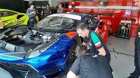 Tim T2 Motorsports mempersiapkan mobil balapnya.