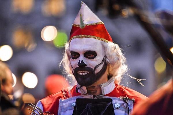Seorang peserta parade menghias wajahnya menjadi seperti tengkorak saat ikut serta dalam karnaval hantu di Cologne, Jerman.