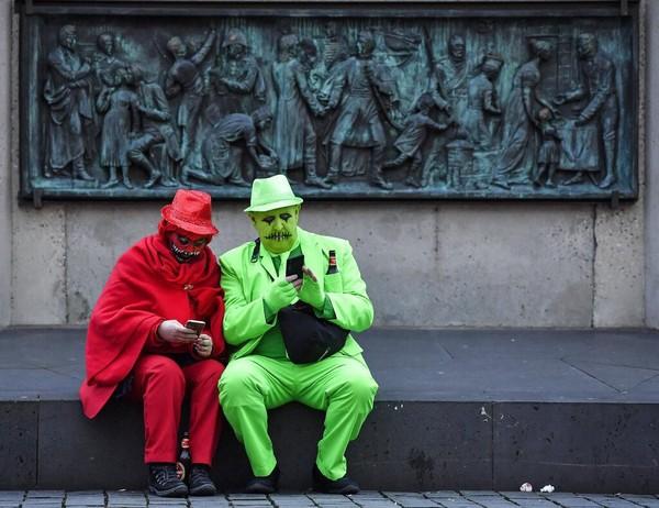Dua orang peserta mengenakan kostum dan menghias wajah mereka menjadi menyeramkan saat mengikuti karnaval hantu di Jerman.