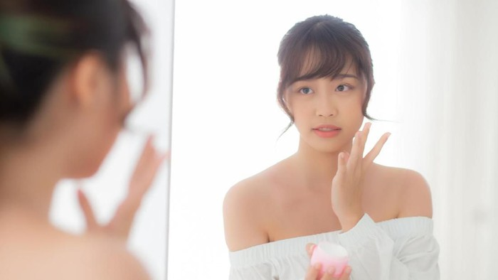 Beautiful portrait young asian woman applying cream moisturizer or lotion skin care cosmetic on face looking mirror, girl with treatment facial, health and wellness concept.