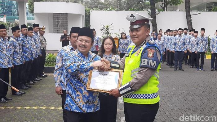 Ketua Ombudsman Amzulian Rifai memberikan penghargaan kepada Bripka Sigit Prabowo yang menggendong warga terkena serangan jantung.