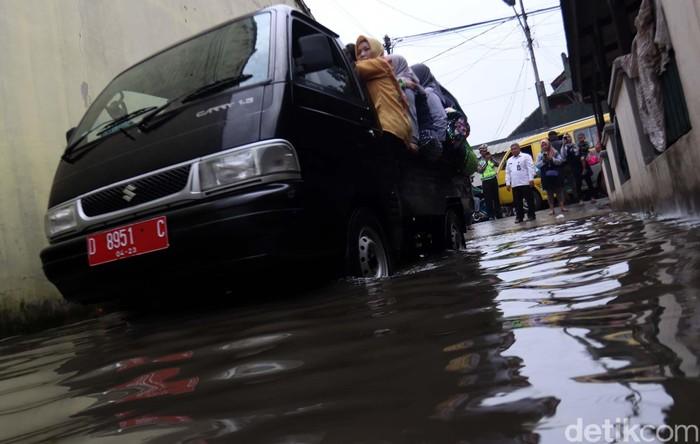 Banjir di Gedebage, Kota Bandung, membuat aktivitas warga terganggu. Siswa TK yang akan berangkat ke sekolah terpaksa diangkut dengan mobil pick up.
