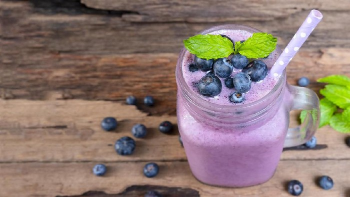 Blueberry smoothies juice beverage healthy the taste yummy In glass drink episode morning on wooden background.