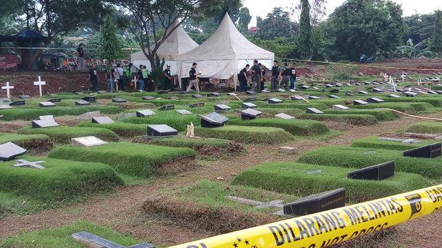 Garis polisi melintang di dekat area makam tempat autopsi dilakukan.