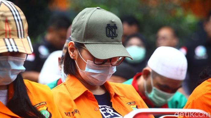 Lucinta Luna dan sejumlah tersangka lainnya dihadirkan saat pemusnahan narkoba di Polda Metro Jaya. Dia tampak memakai topi dan tertunduk lesu.