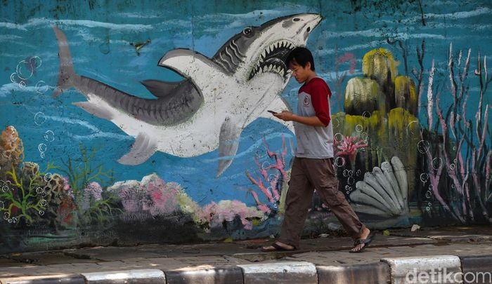 Mural bertema hewan laut menghiasi dinding Jalan Jembatan Tiga Raya di Jakarta. Keberadaan mural itu guna mempercantik kawasan tersebut.
