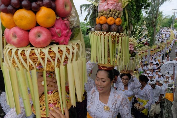 Sejumlah perempuan Bali mengusung Gebogan atau sesajen berisi buah, kue, bunga dan hiasan janur dalam tradisi Mapeed yaitu rangkaian persembahyangan Hari Raya Galungan di Desa Lukluk, Badung, Bali, Rabu (19/2/2020). Tradisi parade sesajen tersebut dilakukan menjelang persembahyangan bersama di Pura Dalem dalam merayakan hari kemenangan