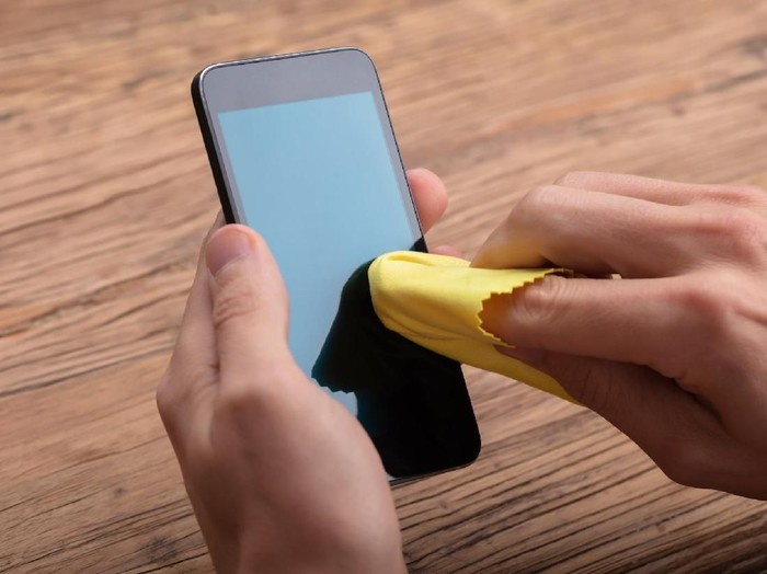 Man Cleaning Mobile Phone Screen With Yellow Cloth Over Wooden Desk