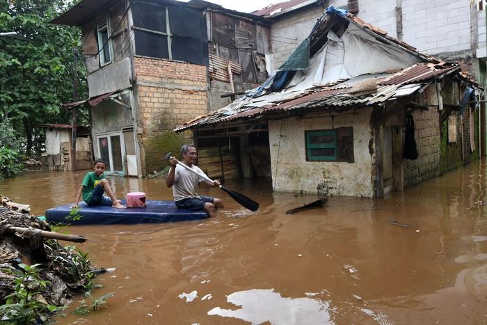 Warga menyusuri jalan perkampungan yang tergenang banjir luapan air Sungai Ciliwung di Cawang, Jakarta, Kamis (20/2/2020). Berdasarkan data Badan Penanggulangan Bencana Daerah (BPBD) DKI Jakarta, terdapat 28 RW di 16 kelurahan dan 10 kecamatan se-Jakarta yang mengalami banjir akibat tingginya intensitas hujan di Jakarta dan sekitarnya sejak Rabu (19/2) malam hingga Kamis pagi. ANTARA FOTO/Aditya Pradana Putra/ama.   *** Local Caption ***